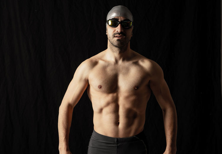 Portrait of shirtless man standing against black background