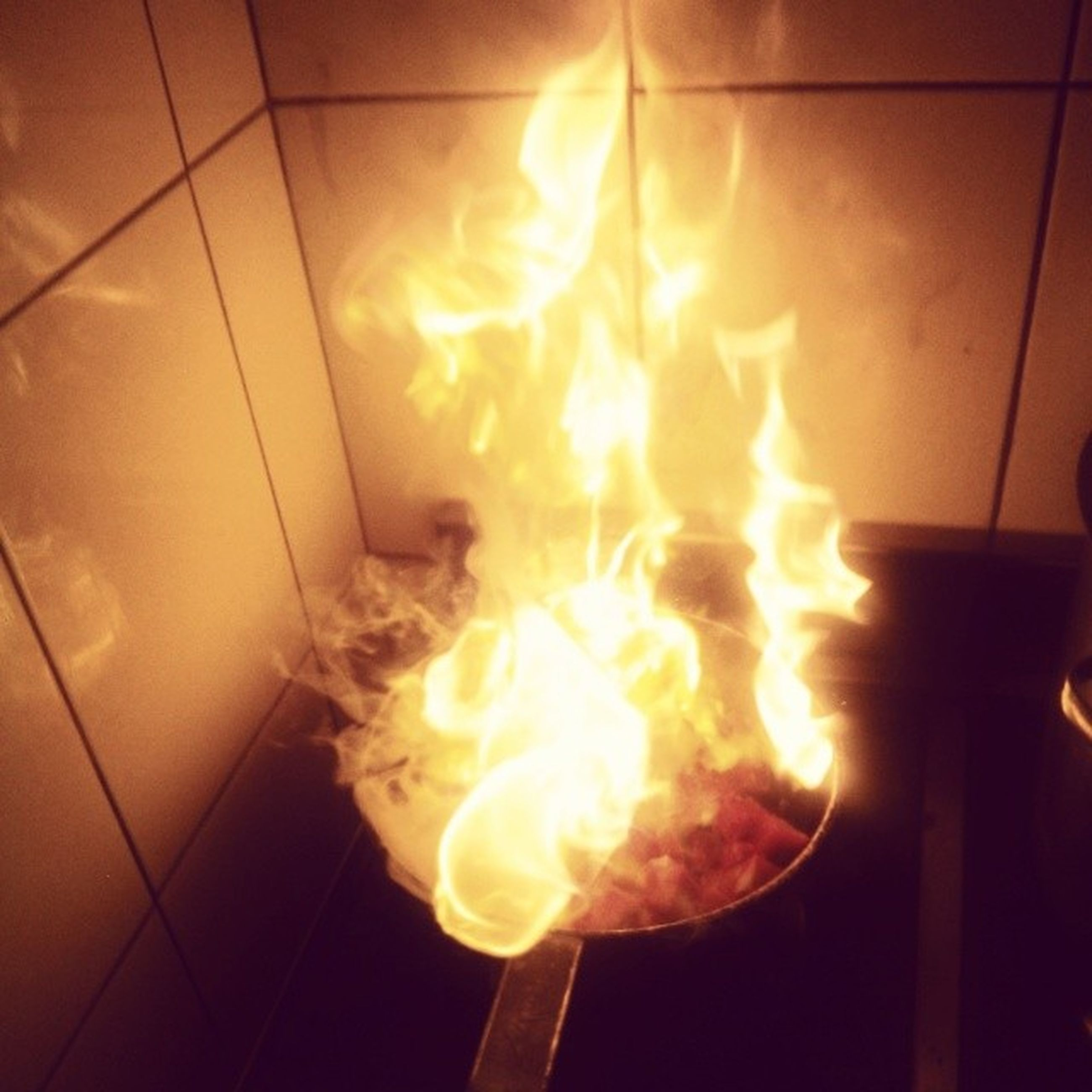 indoors, flame, heat - temperature, illuminated, burning, fire - natural phenomenon, glowing, light - natural phenomenon, lighting equipment, close-up, night, fire, lit, no people, electricity, wall - building feature, yellow, high angle view, metal, orange color