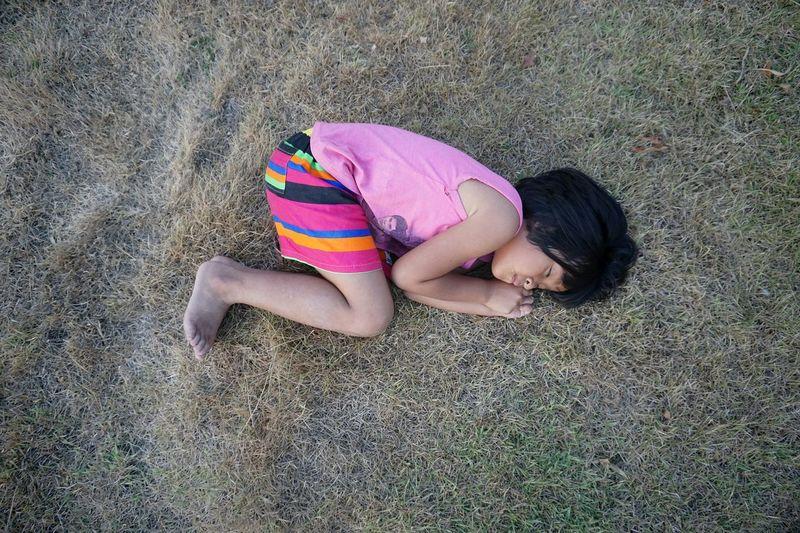 High angle view of girl lying on land