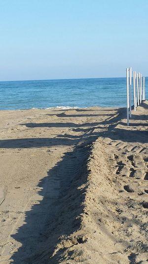 Metallic Poles On Beach Against Clear Sky