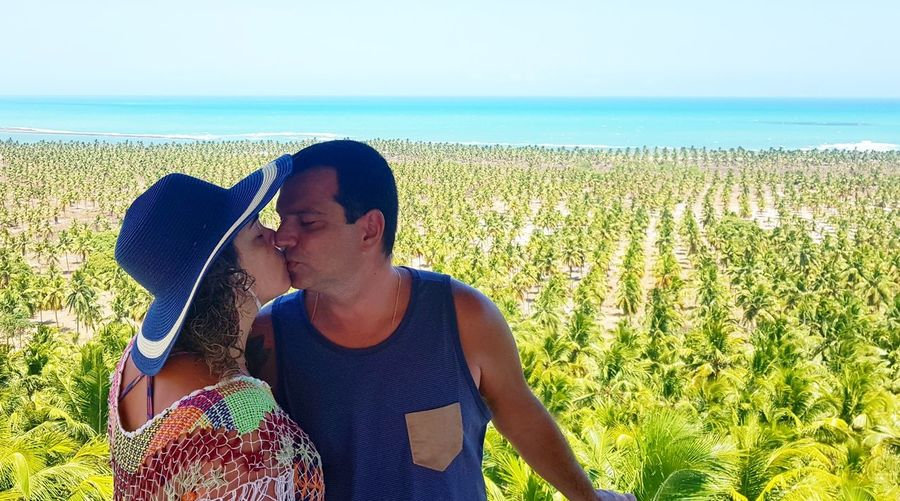 Couple kissing on field against sky