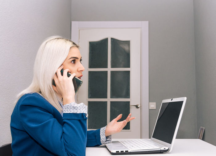 Businesswoman with laptop on desk talking mobile phone in office
