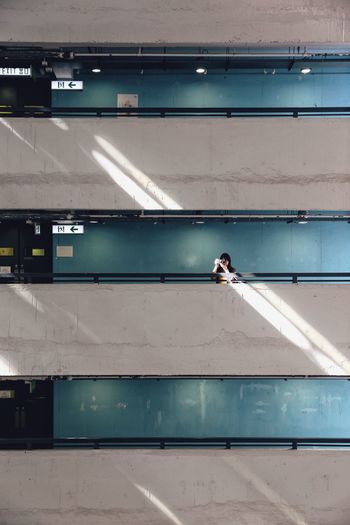Mid distance view of woman photographing in building corridor