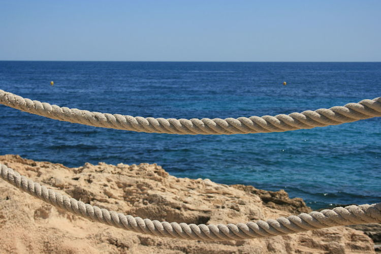 "Marine rope with rocks and blue sea water on background"". Beach Beauty In Nature Blue Clear Sky Horizon Horizon Over Water Land Nature Rock Scenics - Nature Sea Sky Tranquil Scene Tranquility Water"