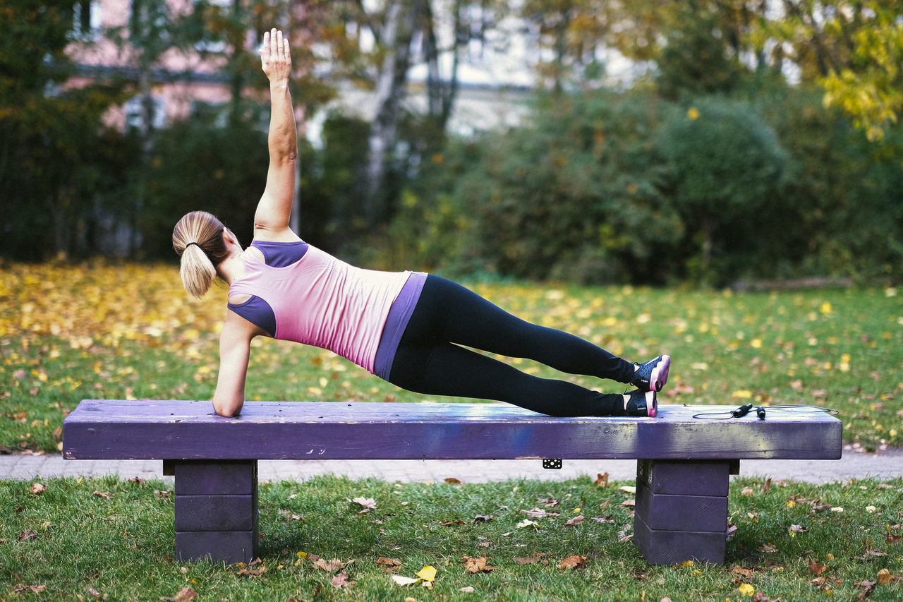 exercising, healthy lifestyle, lifestyles, sports clothing, full length, balance, one person, wellbeing, activity, real people, young adult, yoga, women, tree, outdoors, young women, strength, leisure activity, vitality, motion, day, grass, beauty in nature, nature, only women, one woman only, adult, people, adults only