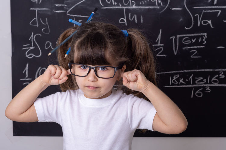 Portrait of cute girl with hands covering ears standing against blackboard