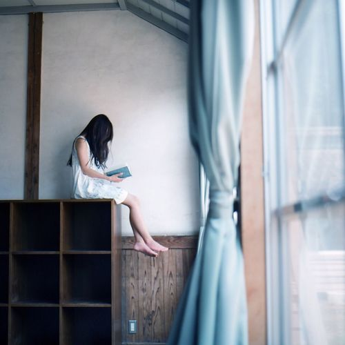 Girl Sitting On Shelf And Reading A Book