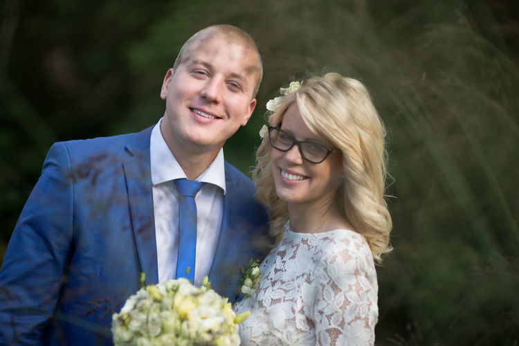 Portrait of smiling bridal couple standing at park