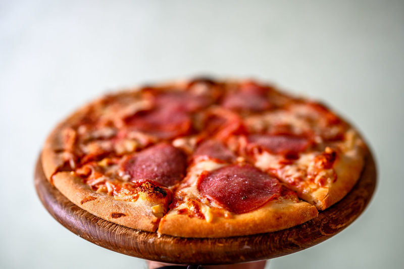 Close-up of pizza on table against white background