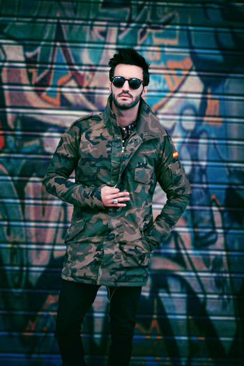 Portrait of handsome young man wearing sunglasses while standing against graffiti on shutter