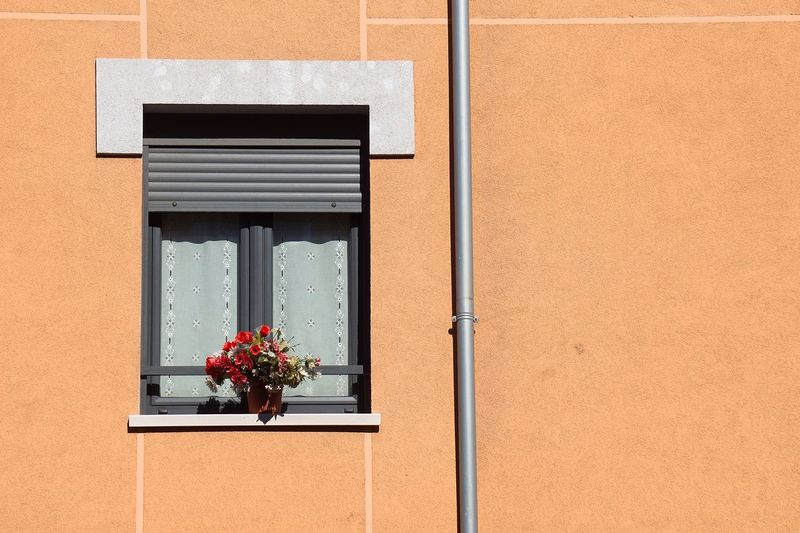 Window on the orange facade of the house in bilbao city spain
