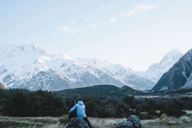 Rear view of couple looking at snowcapped mountains against sky