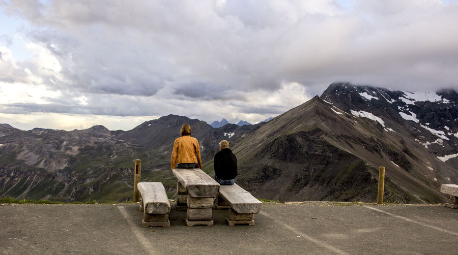 Rear view of man and woman sitting against mountain