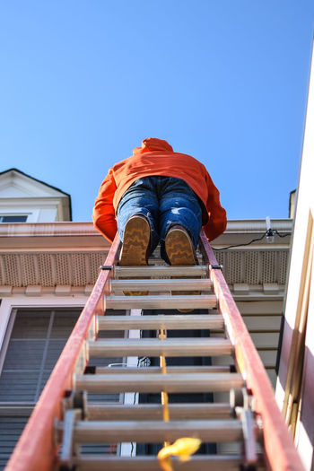 Low Angle View Of Woman Standing On Ladder By House