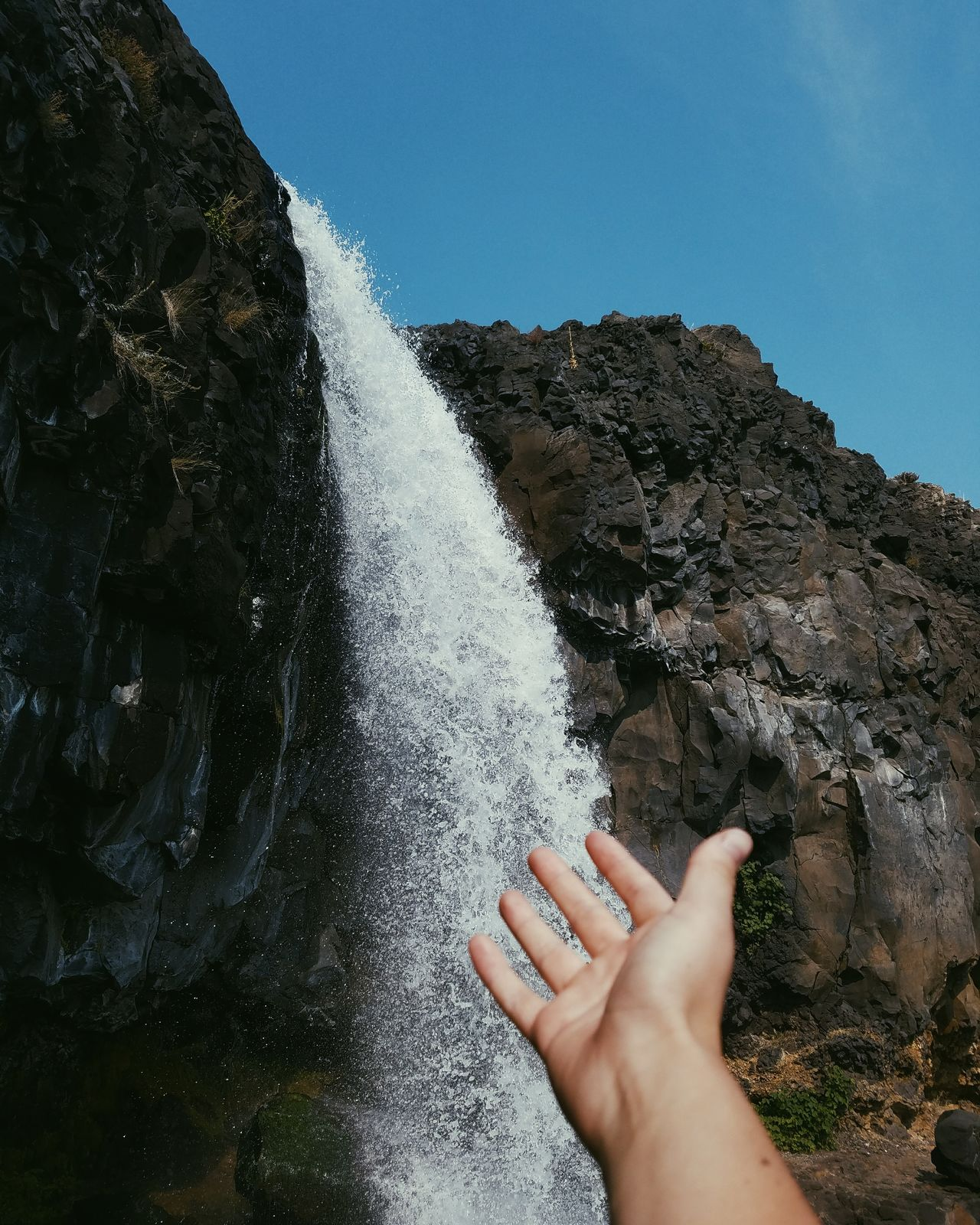 Cropped hand of woman by waterfall against sky