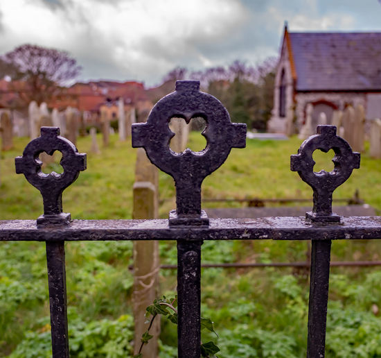 Close-up of metal fence in cemetery