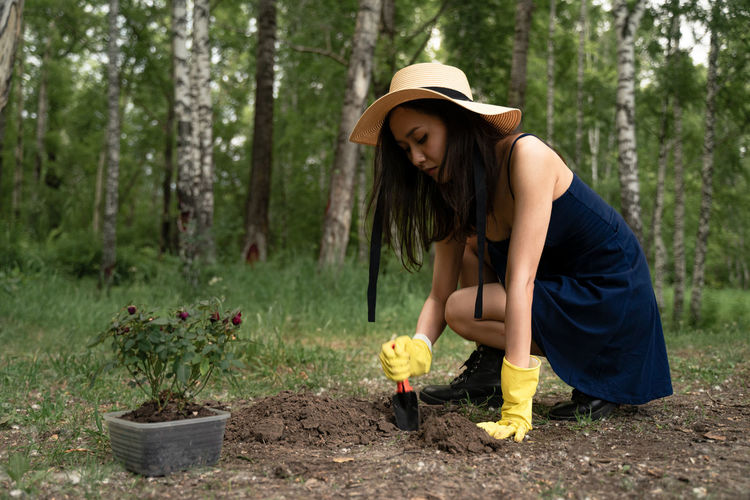 Young woman wearing hat while holding flowers on land