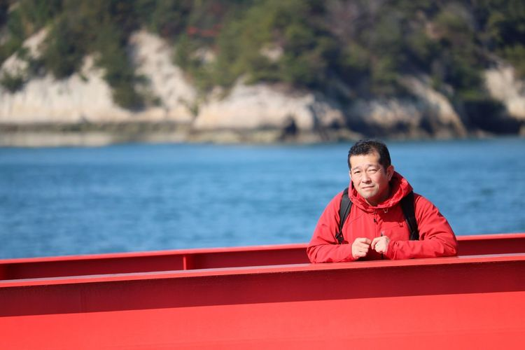 Portrait of man on red boat against sea