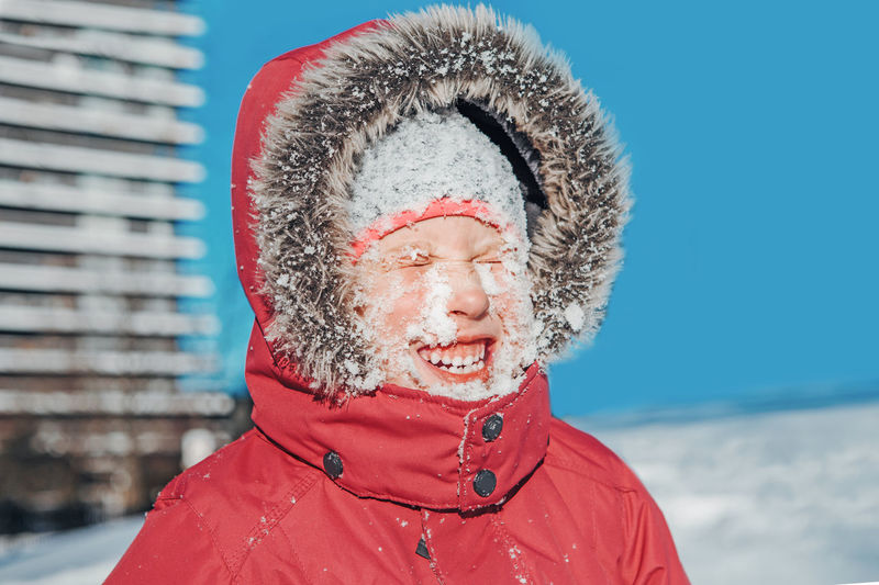 Funny cute adorable caucasian smiling girl in red jacket parka squinting eyes from bright sun.