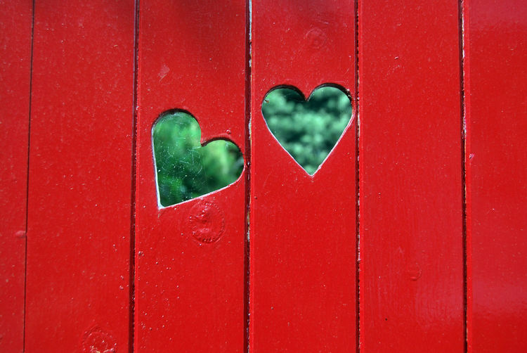 Close-up of heart shape on red wall