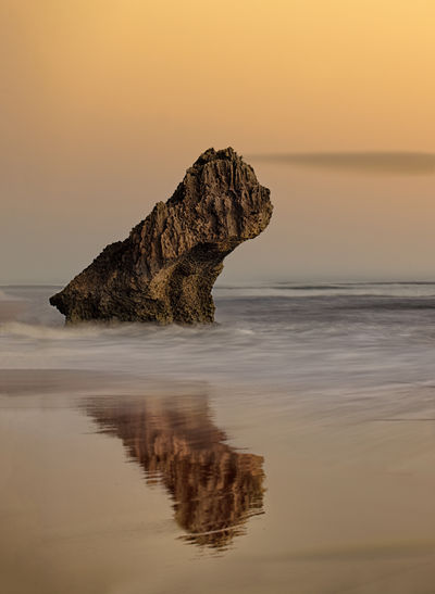 Rock in sea against sky during sunset