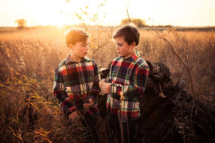 Siblings on field against sky