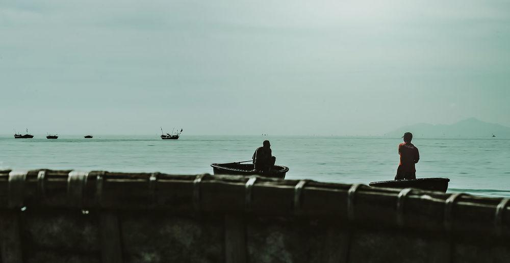 People sitting on sea against sky