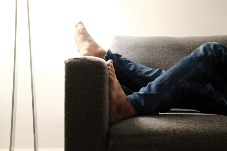 Low section of man relaxing on sofa