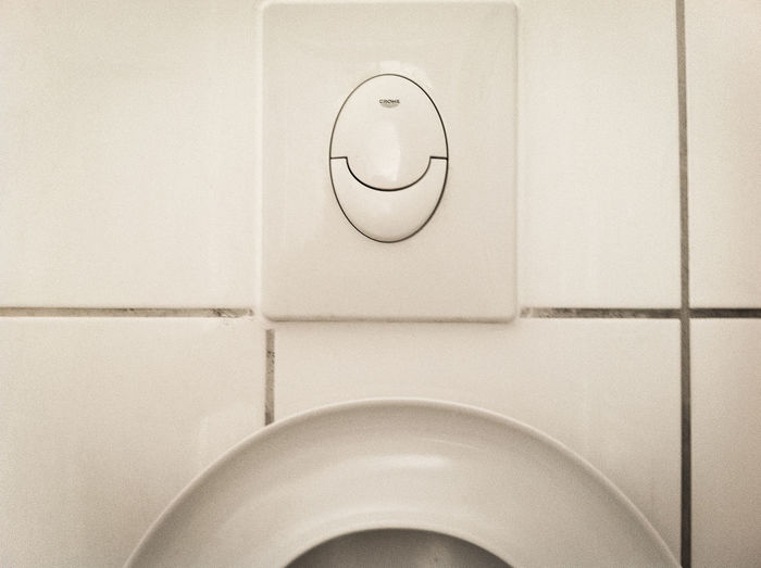 Close-up of toilet seat with water push button Circle Home Interior Indoors  Pattern Push Button Simplicity Still Life Technology Tiles Wall Wall - Building Feature Water White