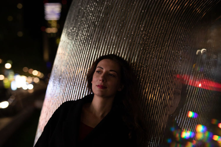 Woman looking away while standing by metal column at night