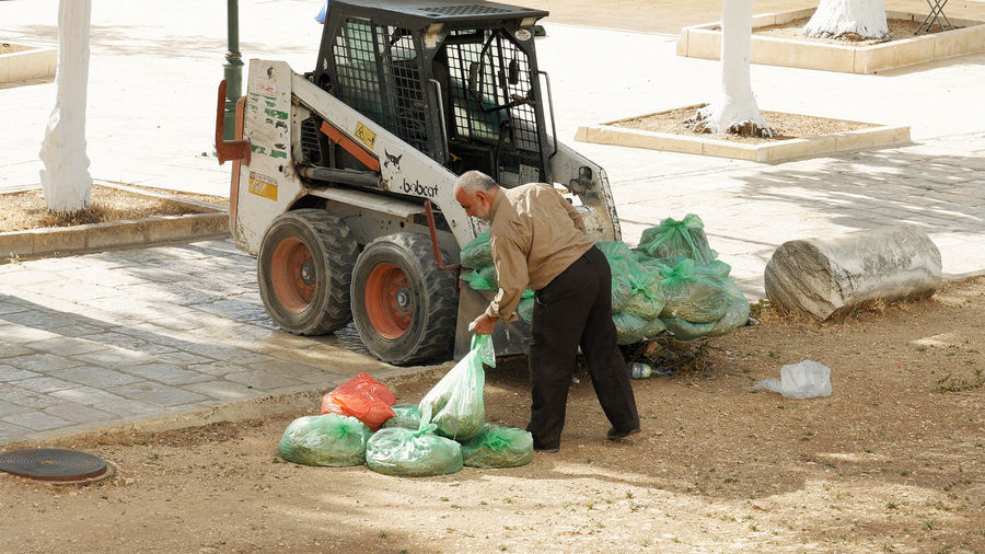 Full length of worker holding plastic bag by forklift on field
