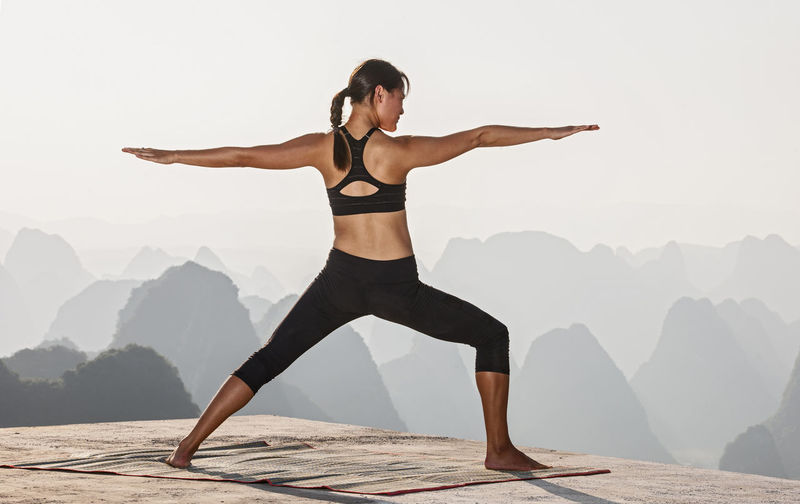 Full length of woman with arms raised against mountain