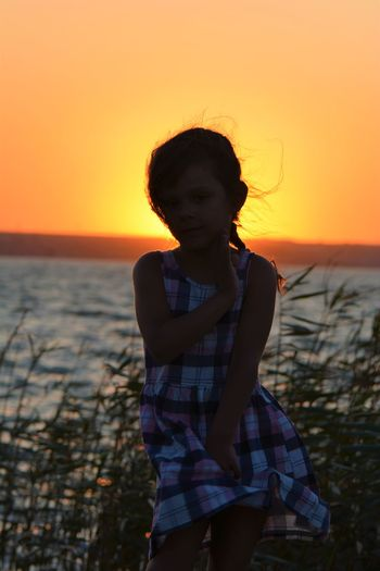 Girl sitting at beach against sea and sky during sunset