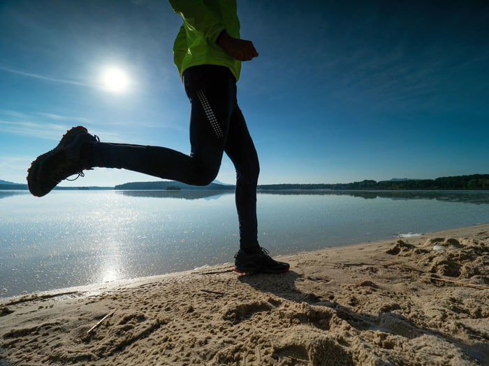 Dynamic silhouette of athlete in compression running tights jogging. man doing intervals workout
