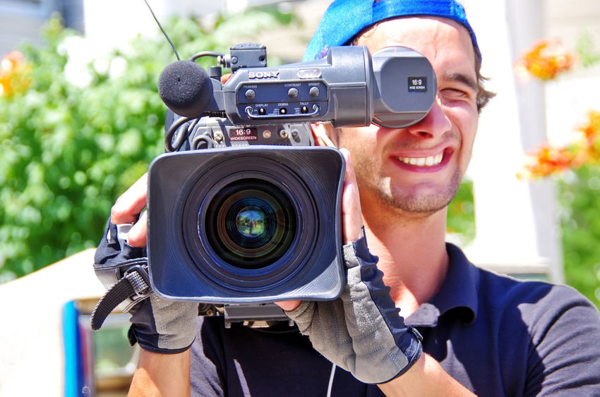 cameraman records live during television show in direct on June 15, 2014 in Reguengos de Monsaraz, Portugal. Camera Camera - Photographic Equipment Digital Camera Filming Front View Headshot Home Video Camera Lens - Optical Instrument Men Occupation People Photographer Photographic Equipment Photographing Photography Themes Portrait Smiling Technology Television Camera Young Adult