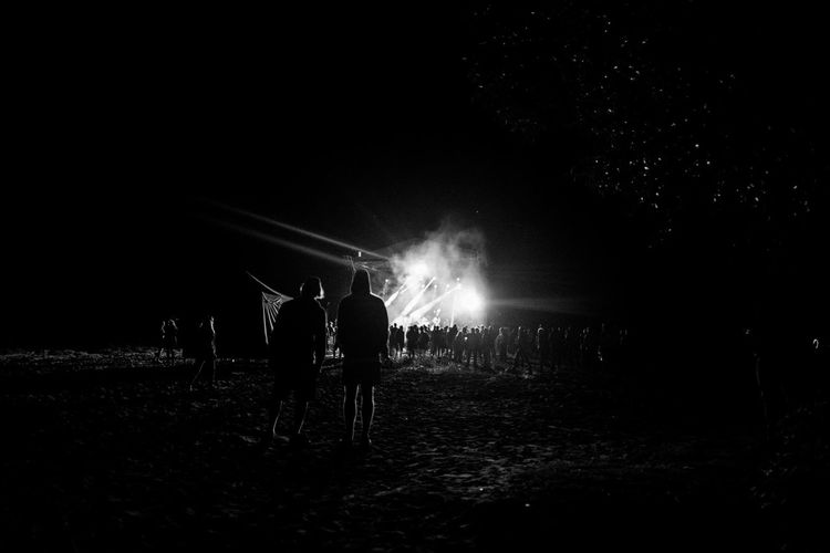 Rear view of people standing on field at night