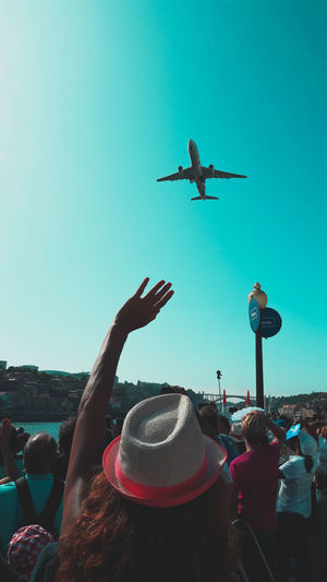 People on airplane against clear blue sky
