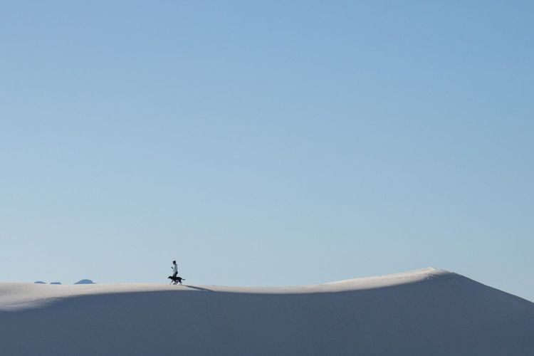 Young woman with dog walking on snow covered hill clear blue sky