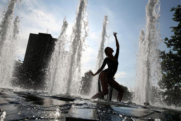 Man splashing water against sky