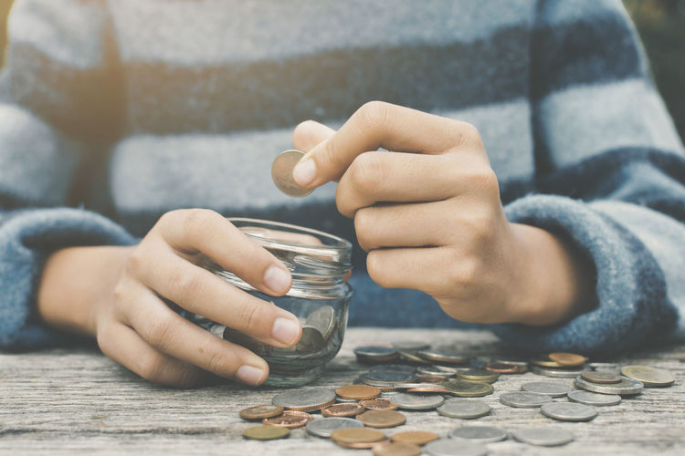Midsection Of Woman Putting Coin In Glass Containers On Wooden Table