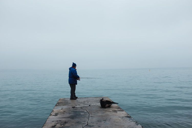 Man Fishing While Standing On Jetty Over Sea Against Clear Sky