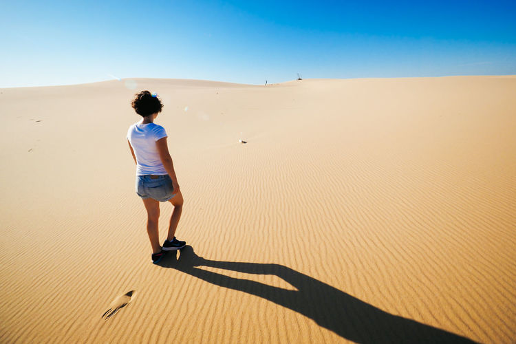 Rear view of woman walking on sand against clear sky at desert during sunny day