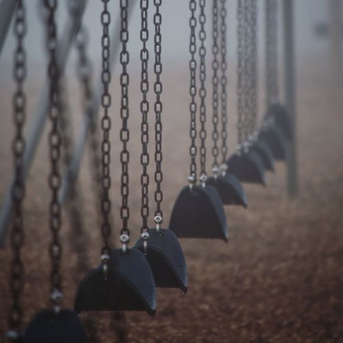 Close-up of empty swings at playground