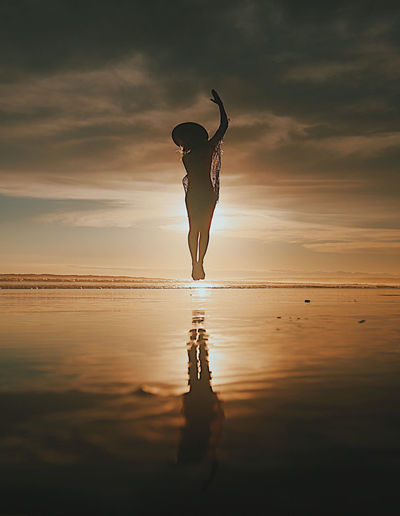 Silhouette young woman jumping at beach against sky during sunset