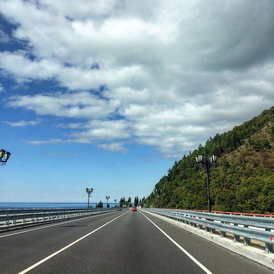 Road Road Transportation The Way Forward Road Marking Diminishing Perspective Tree Blue Vanishing Point Sky Day Tranquil Scene Long Dividing Line Cloud Tranquility Outdoors Crash Barrier White Line Surface Level Solitude