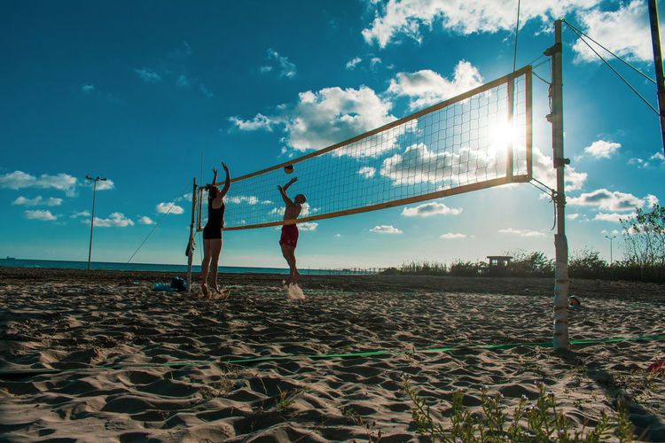 People playing beach volleyball against sky
