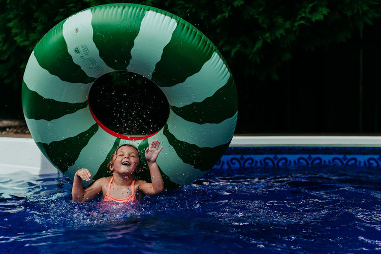 Childhood Leisure Activity Child Water One Person Lifestyles Real People Swimming Pool Pool Girls Front View Enjoyment Fun Day Inflatable  Outdoors Innocence Joy Splashing