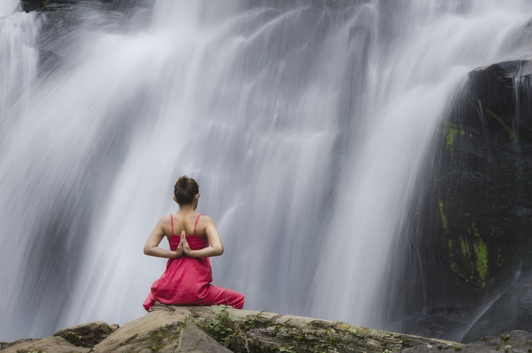 Woman doing yoga in front of a waterfall Beauty In Nature Casual Clothing Day Flowing Flowing Water Leisure Activity Lifestyles Motion Nature Outdoors Rock Rock Formation Sky Tourism Travel Destinations Vacations Water Yoga Yoga In Nature Yoga Pose