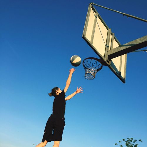 Low angle view of teenage girl playing basketball against clear blue sky
