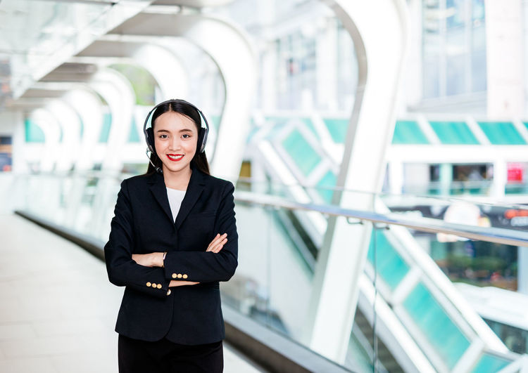 Portrait of smiling businesswoman listening music in corridor